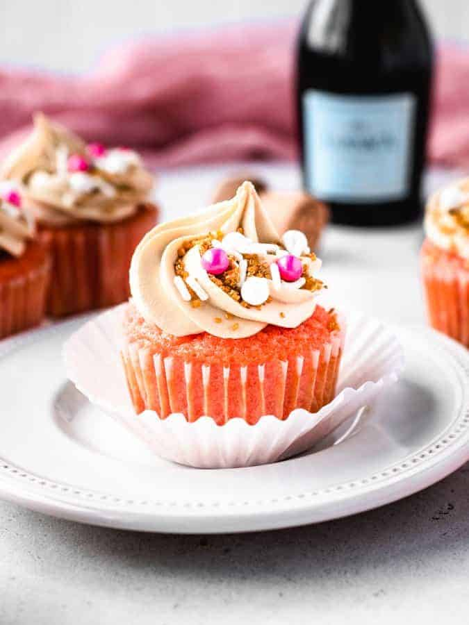 Pink Champagne cupcake on a white plate with bottle of champagne behind it