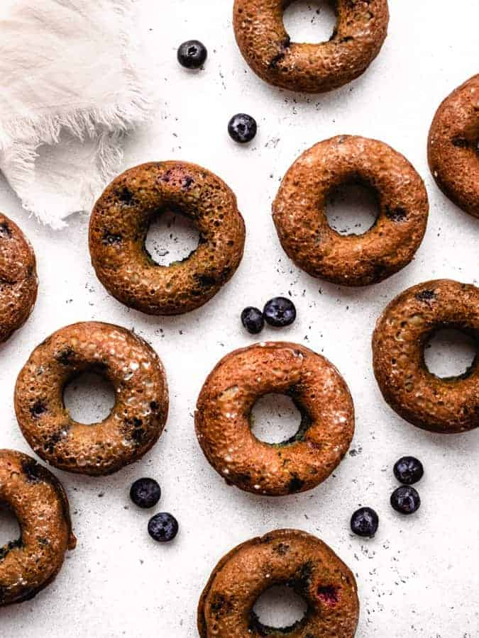overhead of baked blueberry donuts with blueberries around