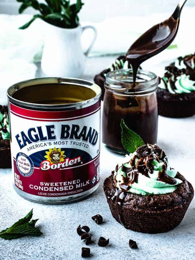 chocolate mint brownie cup next to can of sweetened condensed milk and chocolate ganache