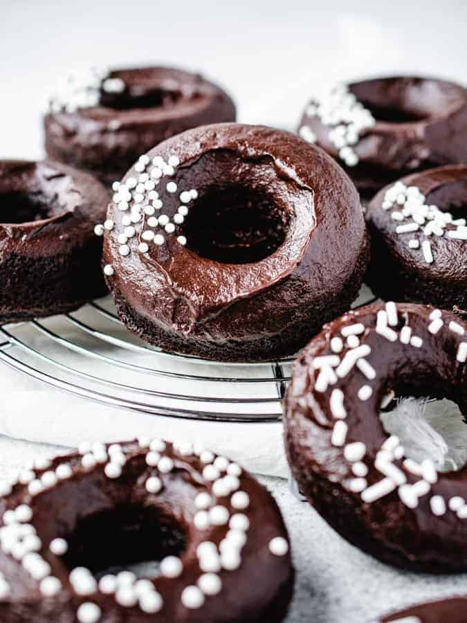chocolate donuts on a wire rack with white sprinkles