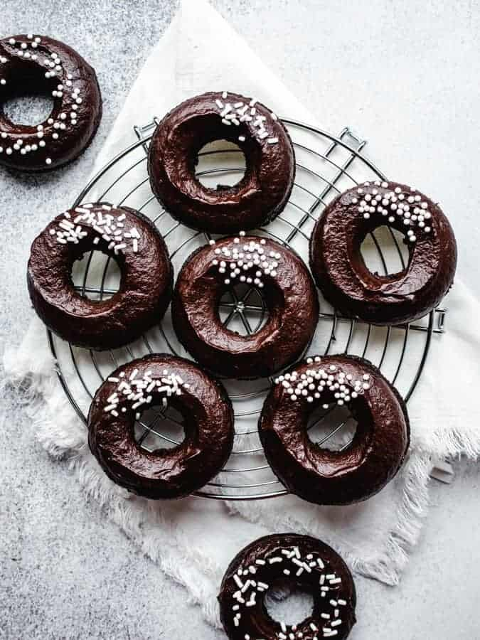 plant-based chocolate fudge donuts on a wire cooling rack with a white napkin beneath