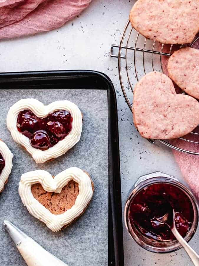Assembling strawberries and cream sandwich cookies with filling and strawberry jam