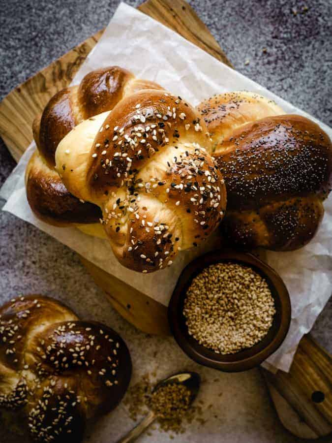 challah rolls on a cutting board with sesame seeds in a bowl
