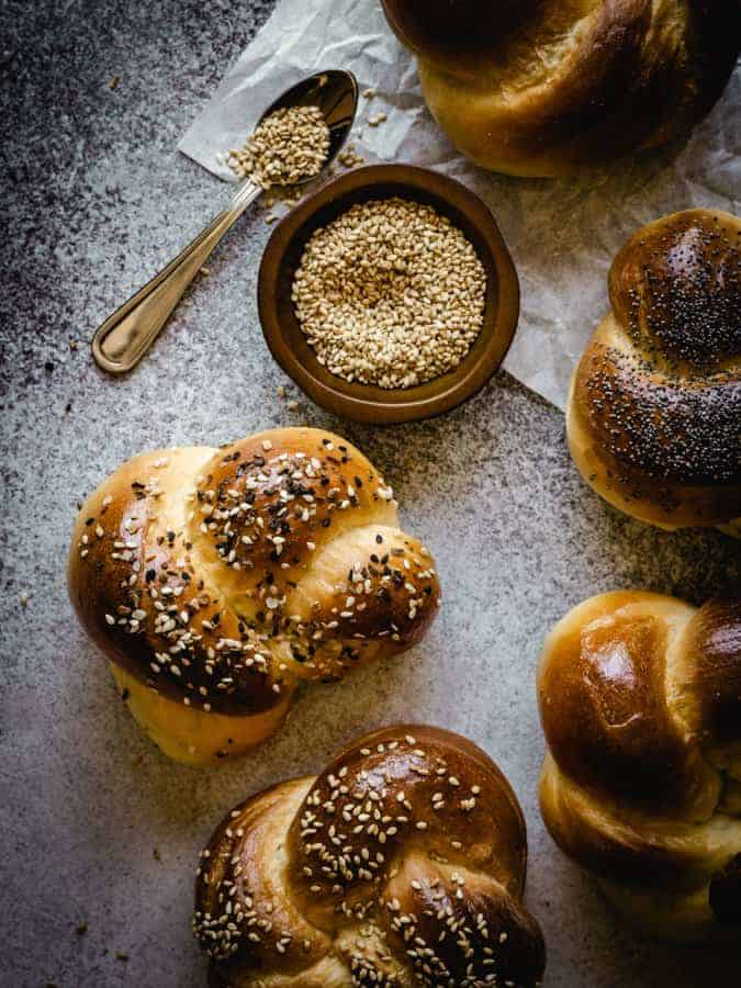 challah rolls with sesame seeds in a bowl and a small spoon