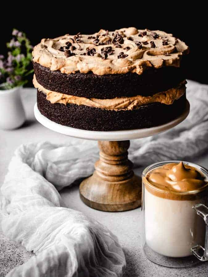 Coffee chocolate cake on a cake stand with dalgona coffee in front and flowers behind