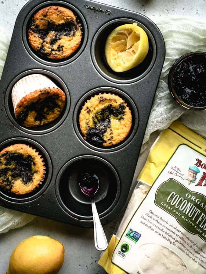 overhead of lemon muffins with blueberry jam in a muffin tin