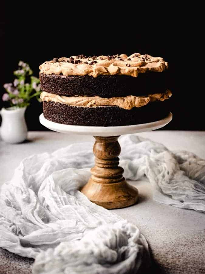 dalgona coffee chocolate cake on a cake stand with linen around and flowers behind