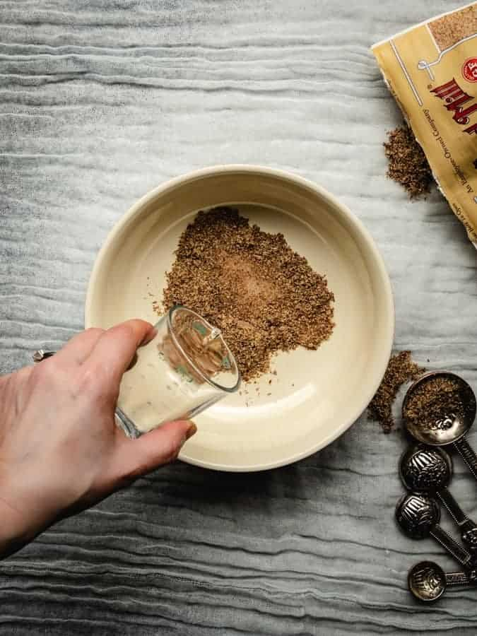 pouring water into flaxmeal to make a vegan flax egg substitute for eggs in a vegan recipe