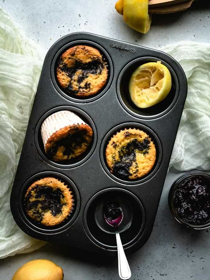 lemon muffins made with coconut flour and swirled with blueberry jam in a muffin pan