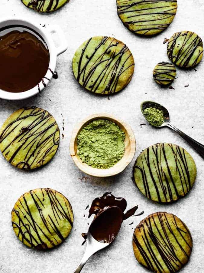 overhead of green tea shortbread cookies on parchment paper drizzled with dark chocolate