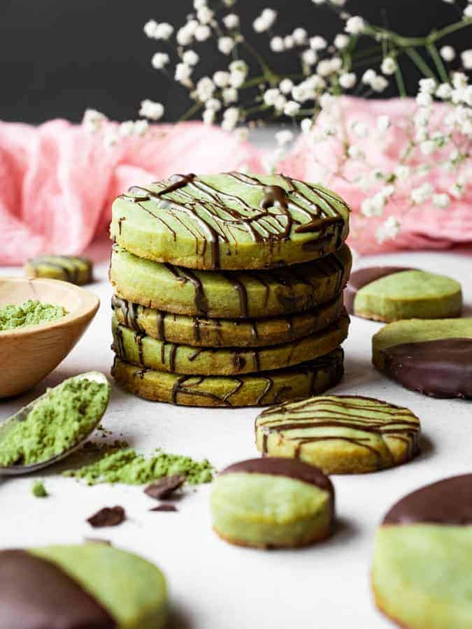 stack of matcha green tea shortbread cookies with flowers behind