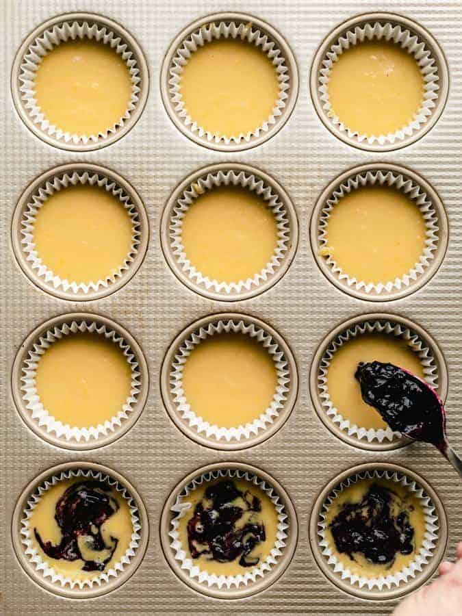 Spooning paleo blueberry jam into lemon muffin batter