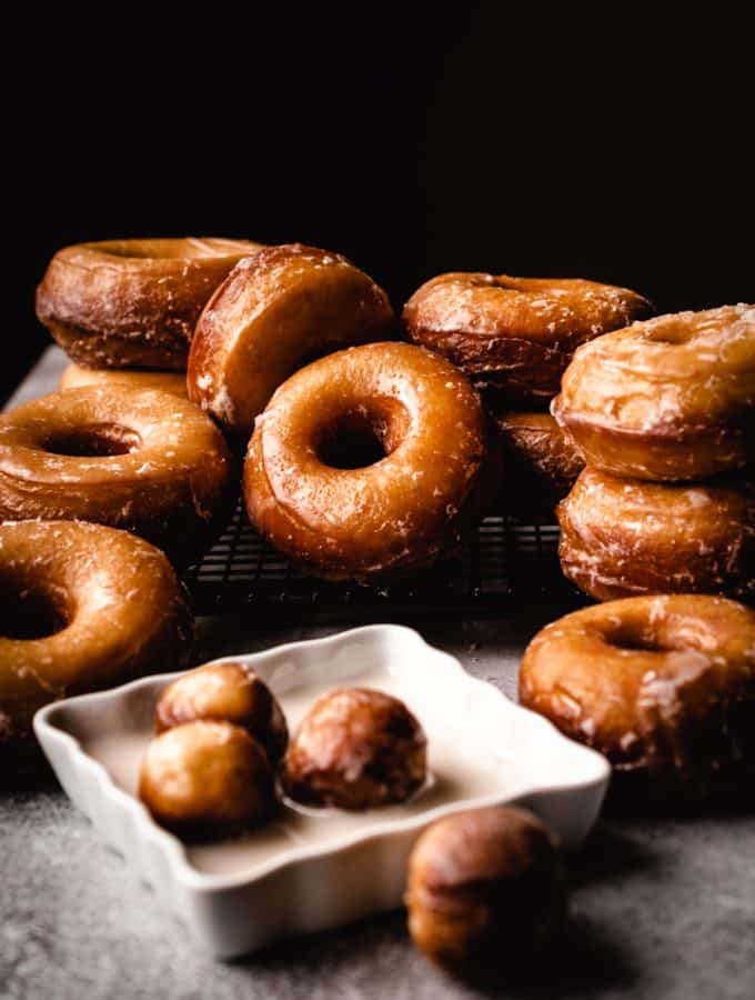 donuts in a pile on a cooling rack with donut holes sitting in glaze