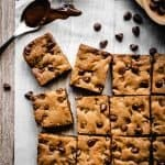 overhead of blondies cut into squares with chocolate chips and melted chocolate on the side