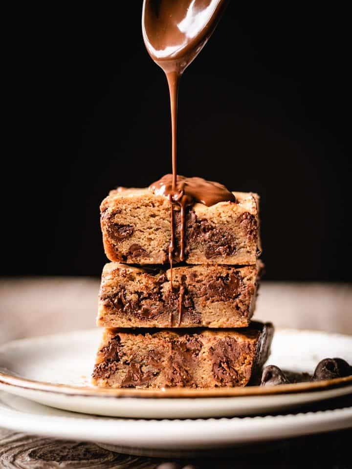 stack of three blondies on a plates being drizzled with melted chocolate