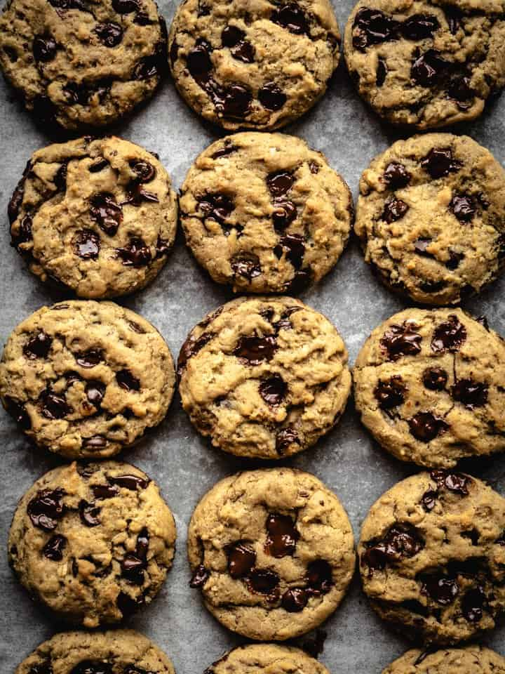 overhead of freshly baked vegan chocolate chip cookies on a baking tray