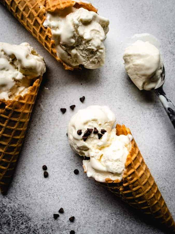 vanilla ice cream cones on a backdrop with mini chocolate chips