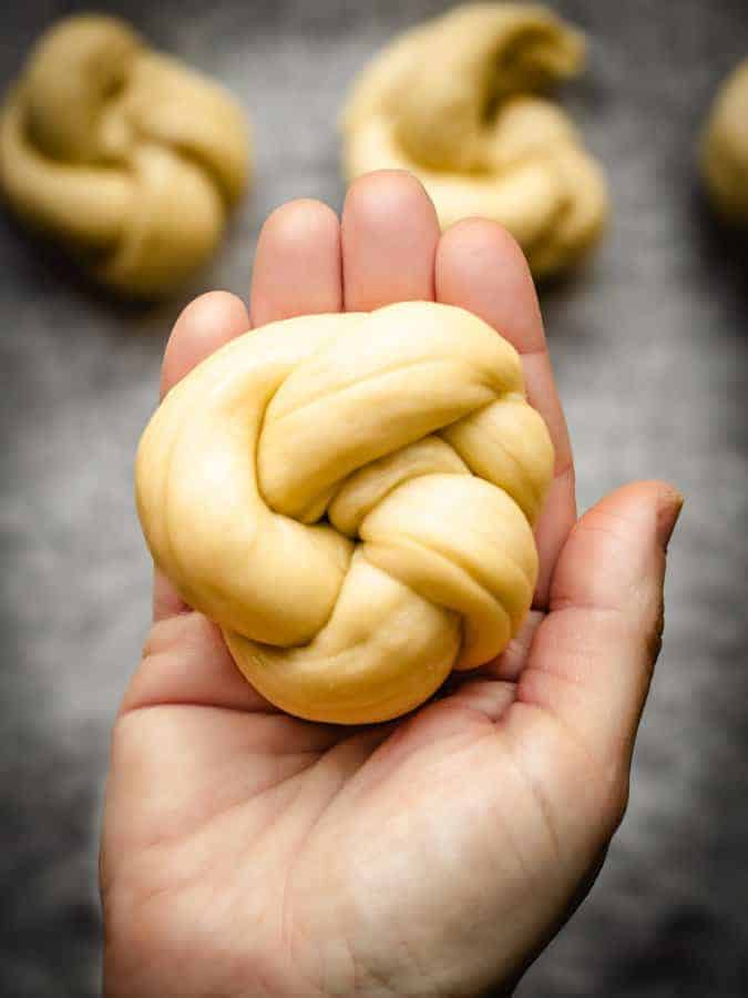 hand holding a knotted challah roll before it's baked