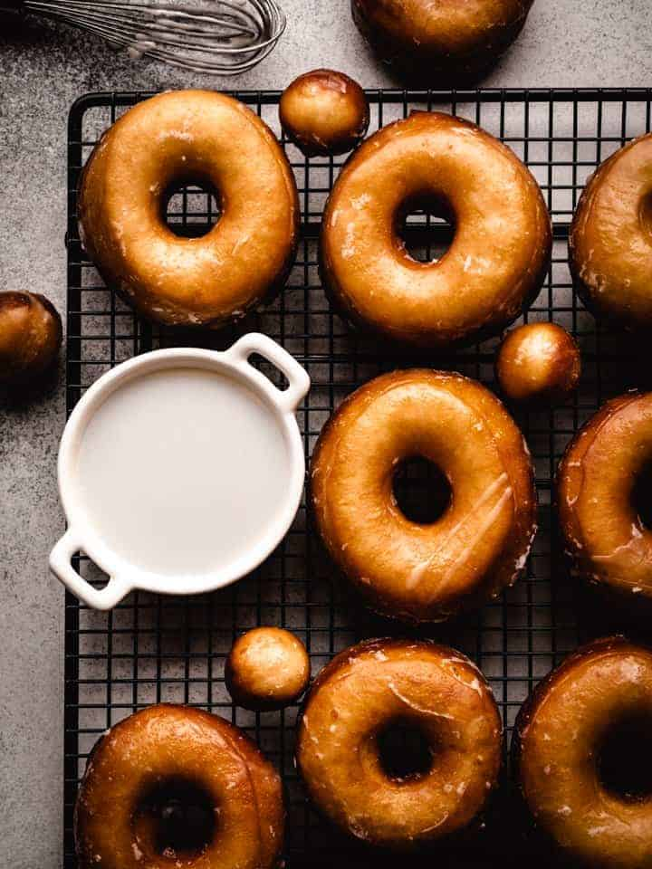 homemade glazed donuts on a wire rack with glaze in a bowl and a whisk