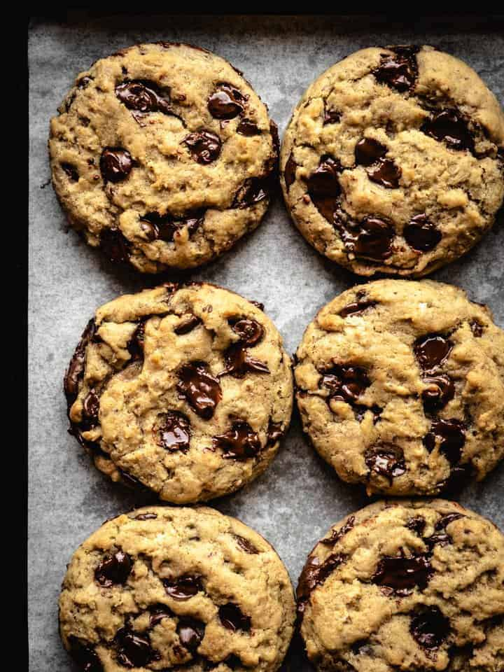 freshly baked plant based chocolate chip cookies on a baking sheet