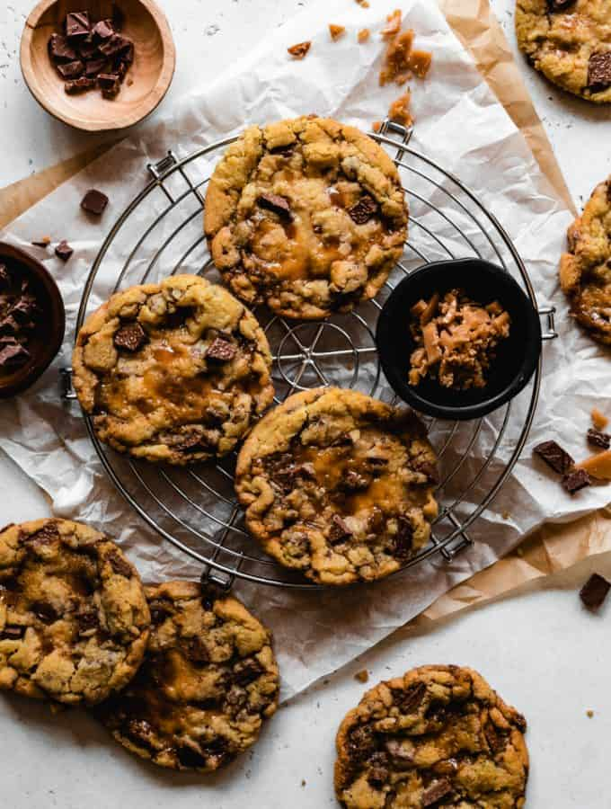 milk chocolate chip toffee cookies on a round cooling rack with ingredients around it