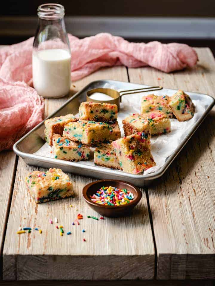 sugar cookie bars with sprinkles on a tray with milk behind it
