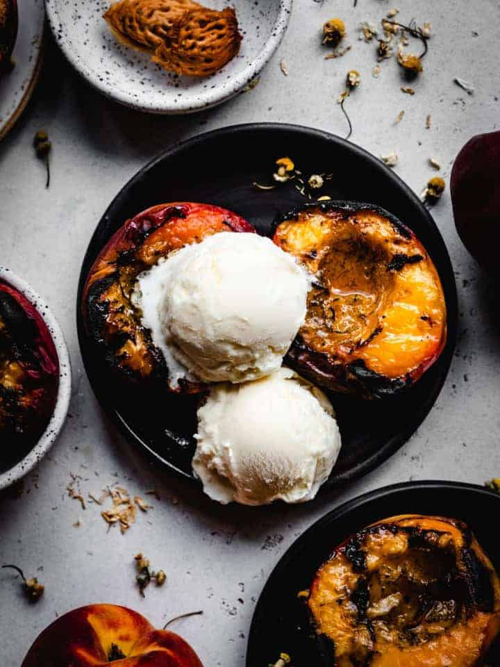 grilled peaches on a black plate with scoops of vanilla ice cream