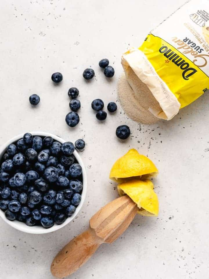 Preparing blueberry jam using fresh blueberries lemons and sugar