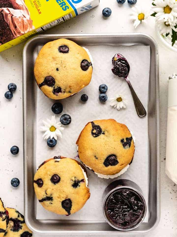 blueberry whoopee pies on a tray with blueberries and flowers around