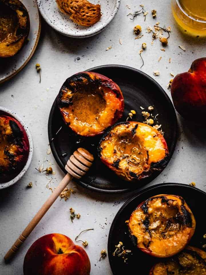 grilled peaches on a black plate with honey