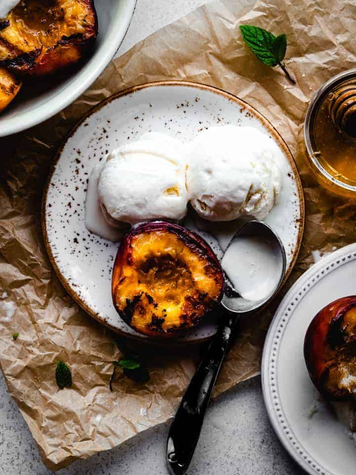 half grilled peach on a plate with two scoops of ice cream