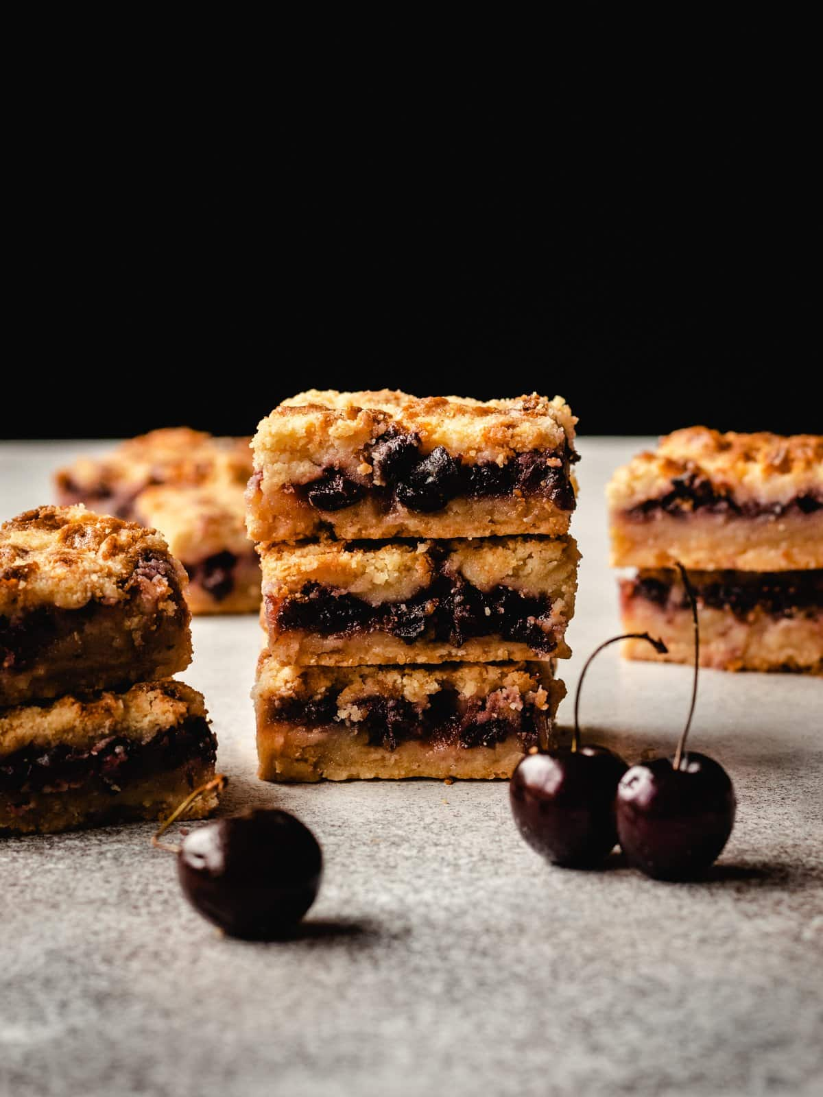 stack of cherry pie bars against a black backdrop