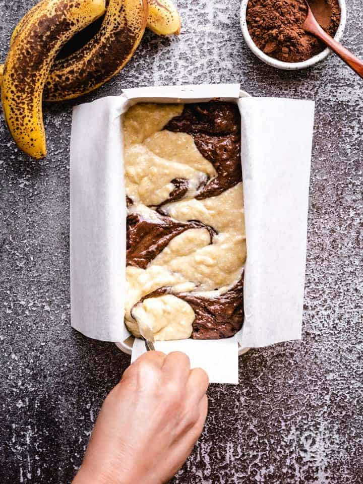 swirling chocolate banana bread in a loaf pan