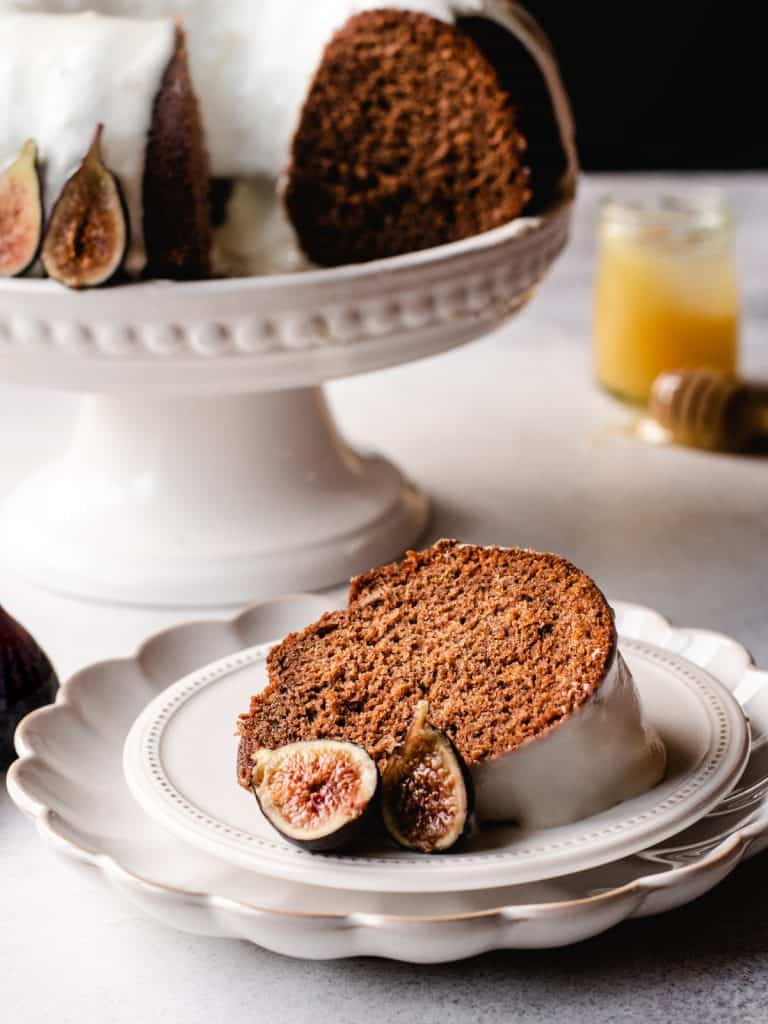 slice of honey cake with goat cheese frosting and figs on a plate