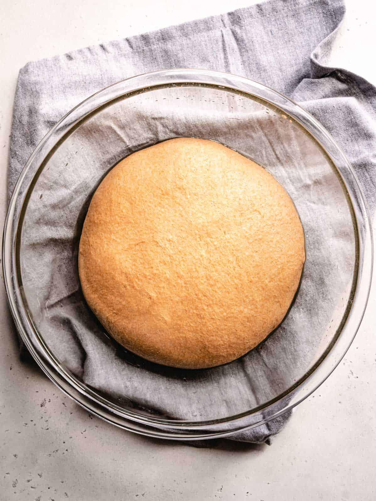 proofed honey wheat sandwich bread in a bowl