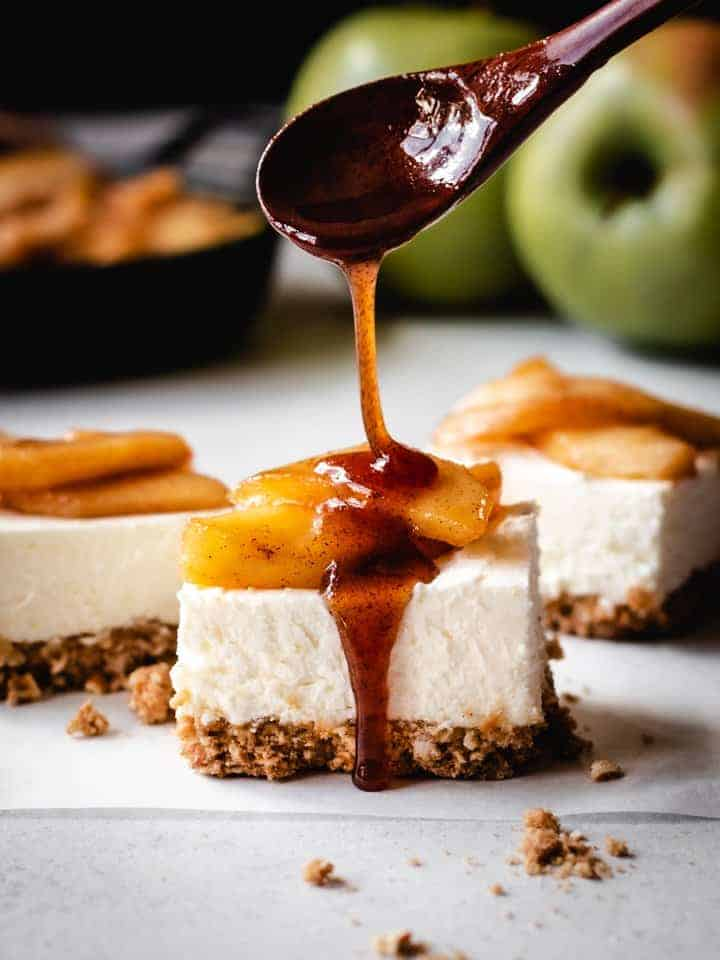 pouring caramel on top of caramel apple cheesecake squares