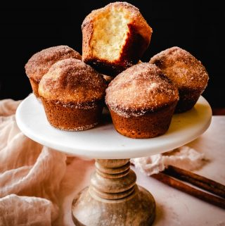 cinnamon sugar donut muffins on a cake stand with bite taken out of one