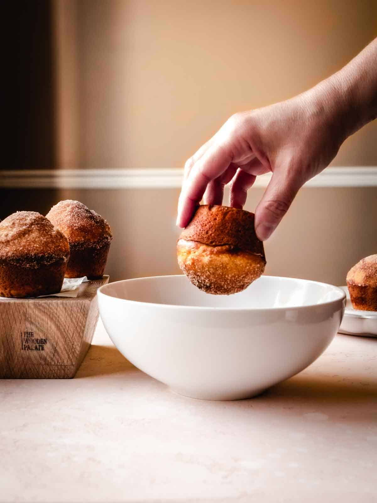 dipping donut muffin in melted butter and cinnamon sugar