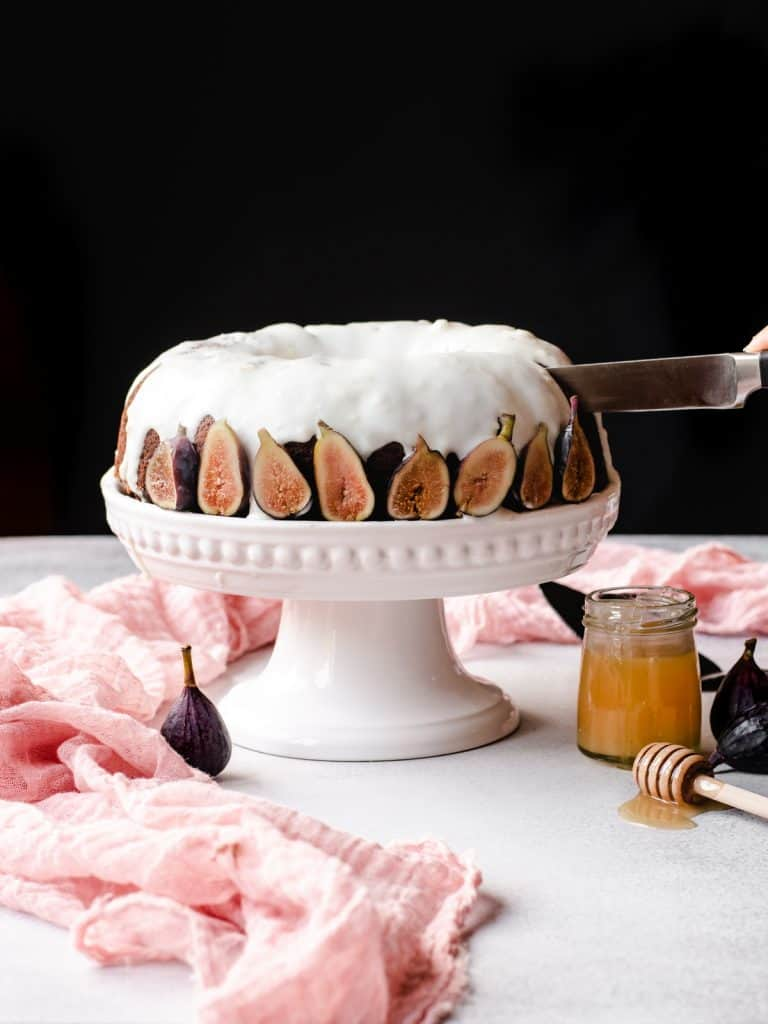 cutting into a honey cake with figs
