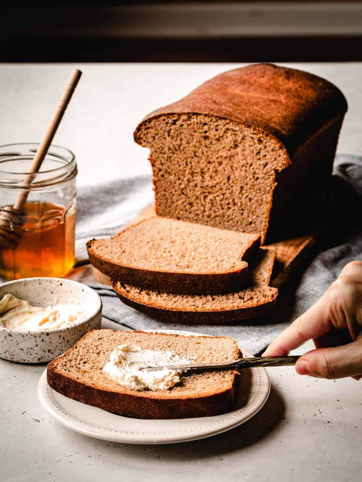 spreading butter on a slice of honey wheat bread