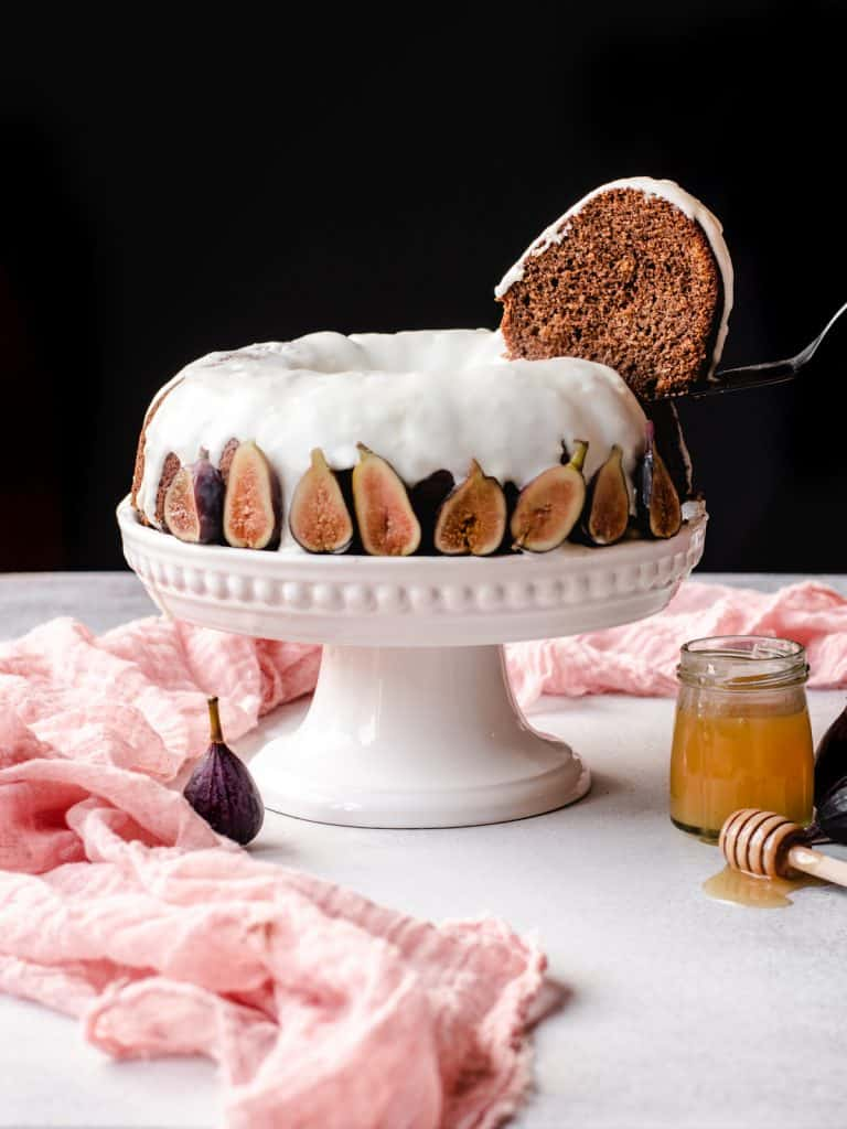 taking a slice out of a honey cake on a cake stand