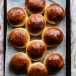 freshly baked brioche buns on a tray