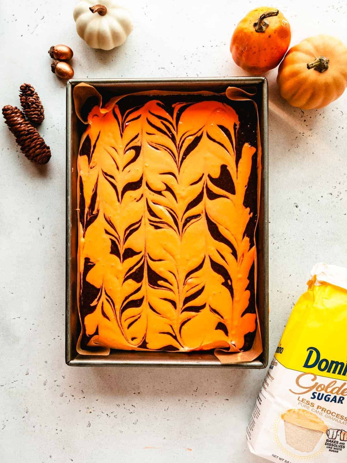 overhead of orange and black swirled cream cheese brownie batter in a pan