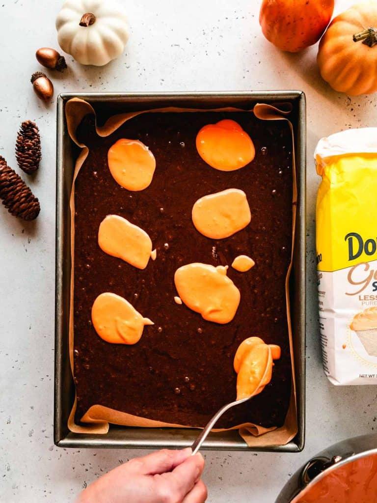 dolloping orange cream cheese mixture onto brownies
