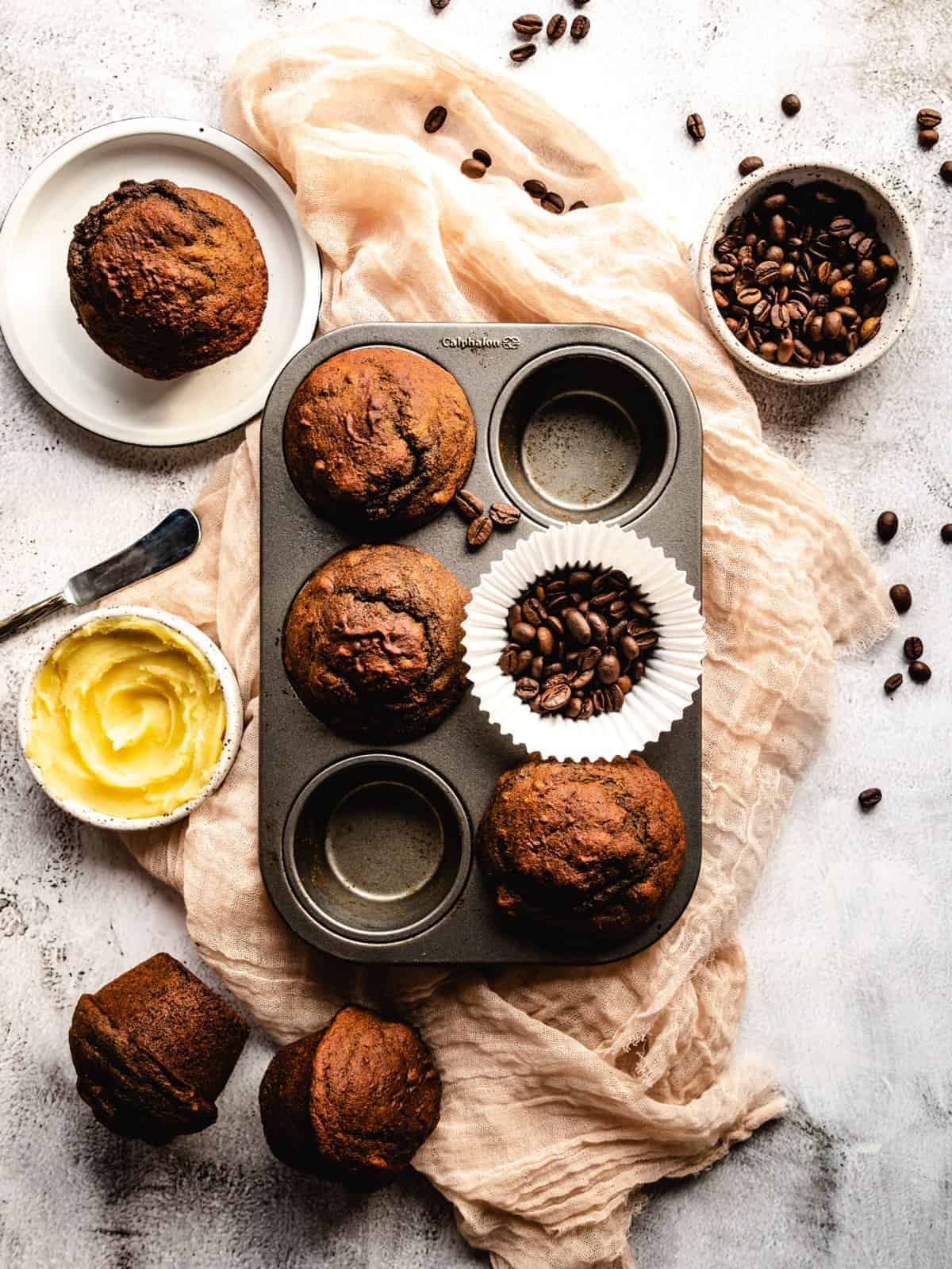 muffins in a tin with butter and coffee beans around