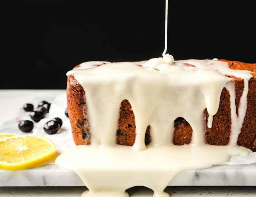 pouring thick lemon glaze over loaf cake