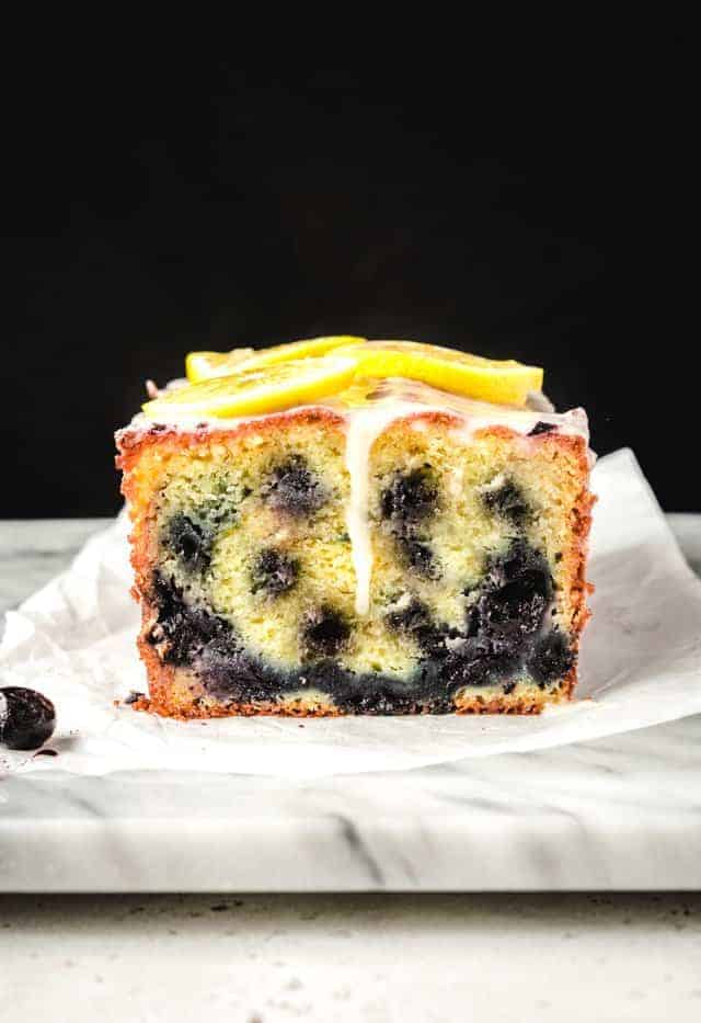 lemon blueberry loaf cake sliced with glaze dripping down the front