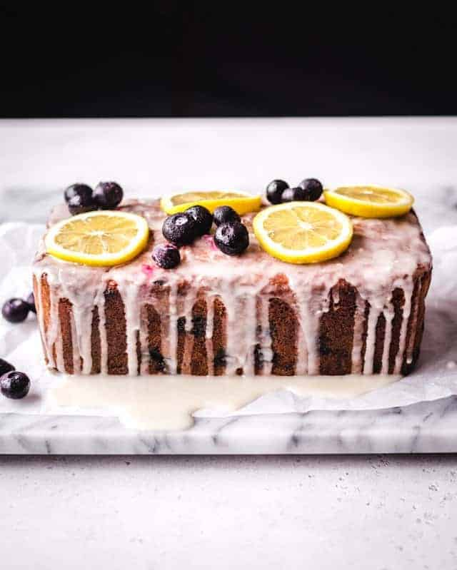 lemon blueberry loaf cake with lemon glaze poured over the top
