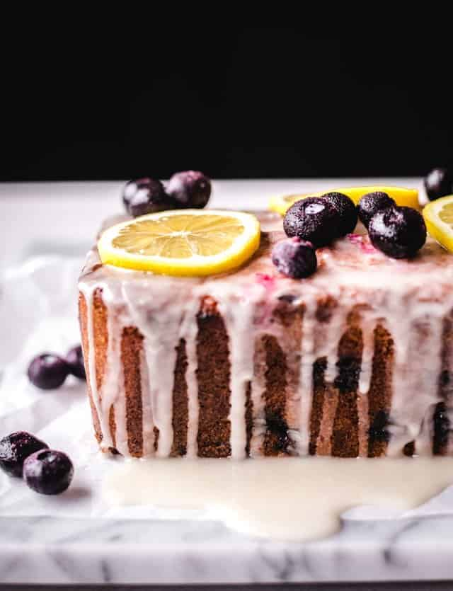 lemon blueberry cake with glaze dripping down the side