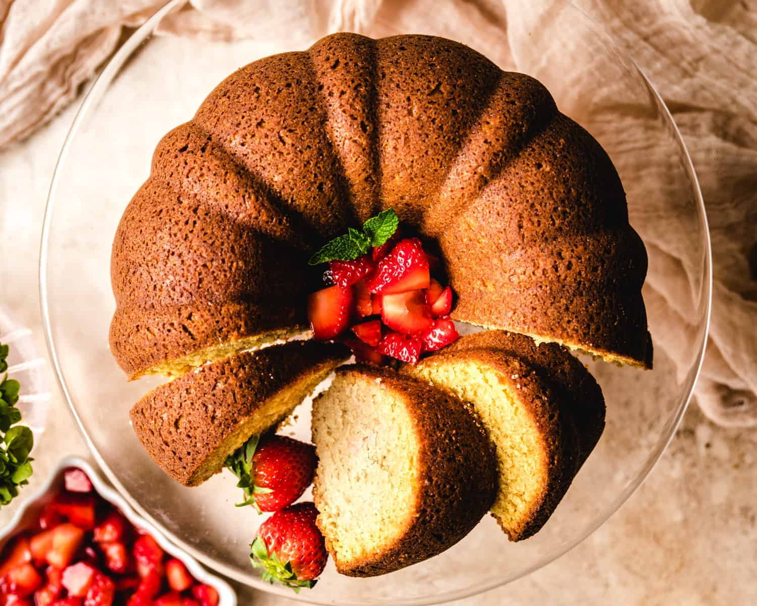 bundt cake on a glass cake stand with slices and strawberries